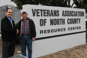 two men by veterans association of north county sign