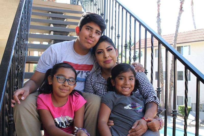 family sitting on steps of apartment building