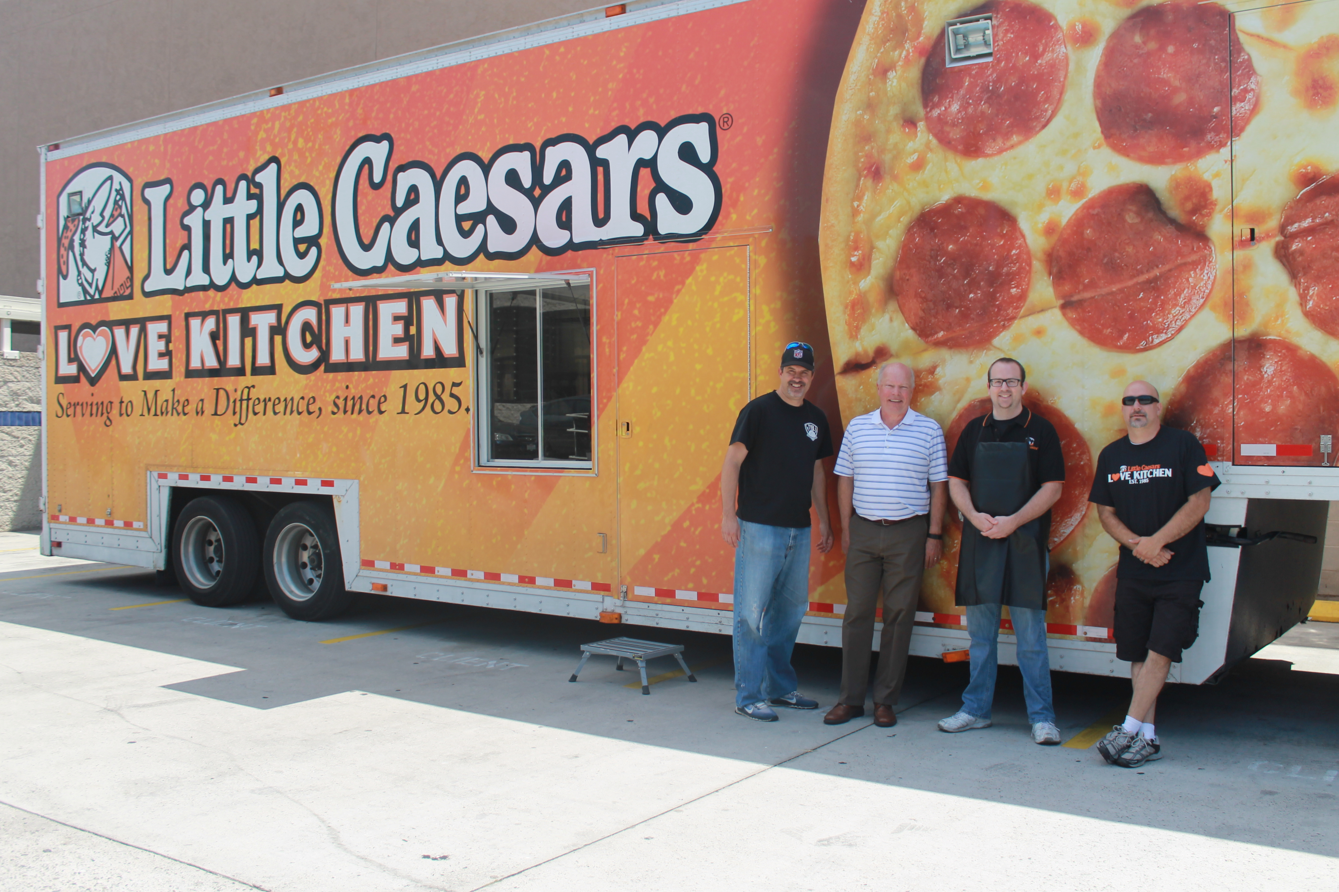 group in front of little caesars truck