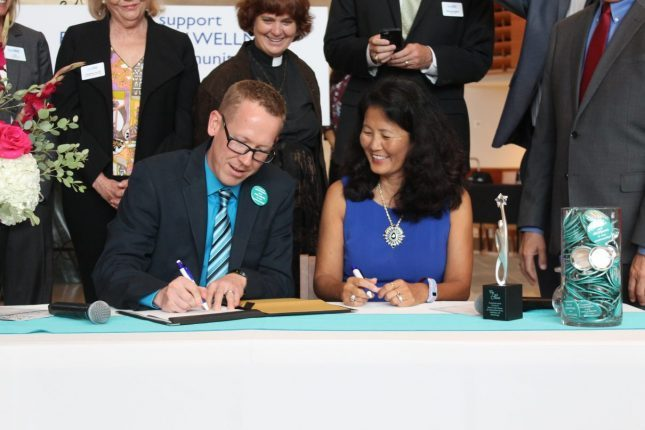 man and woman signing document