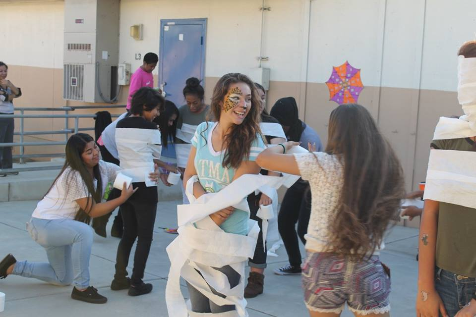 kids wrapping each other in toilet paper like mummies