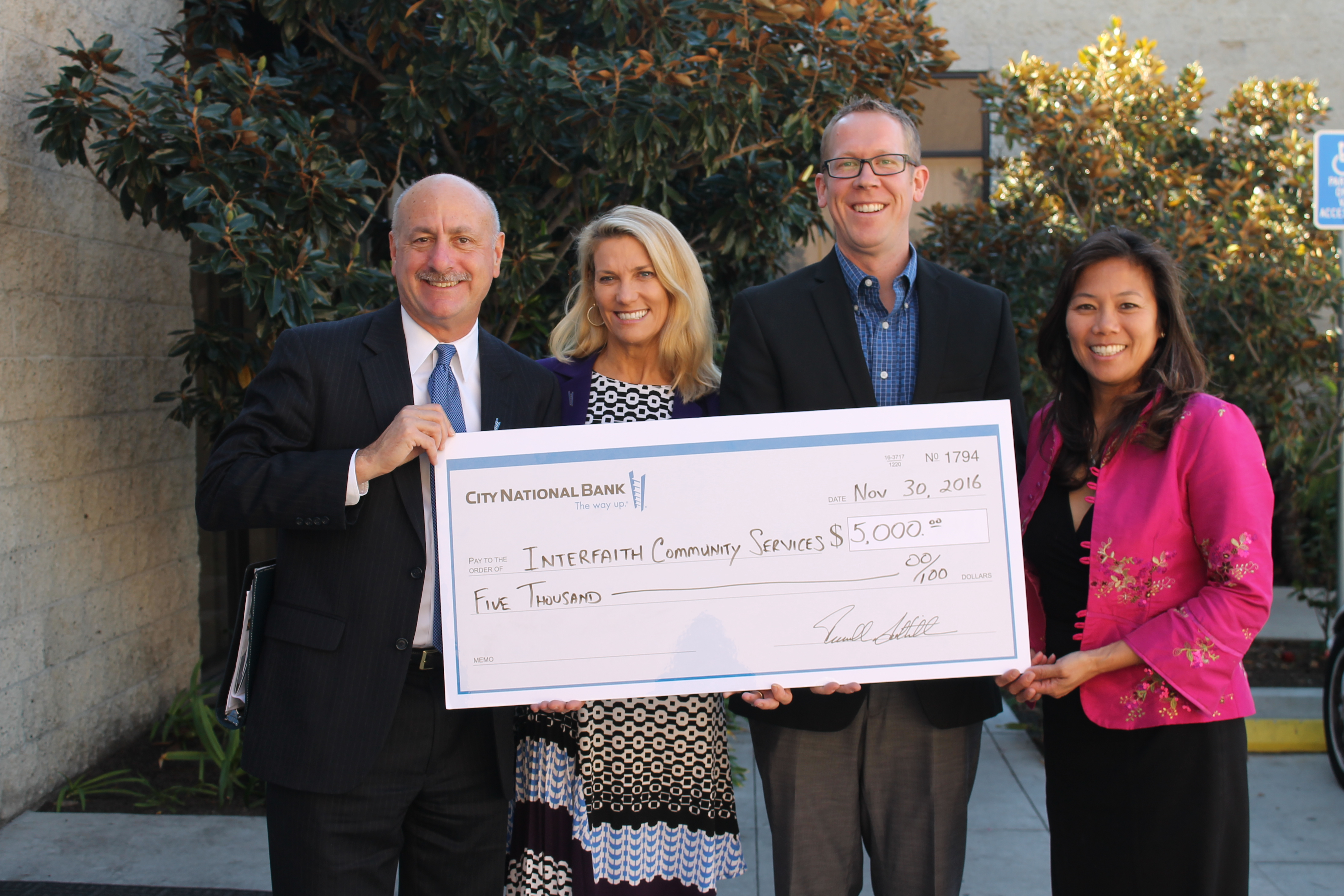 City National Bank dontes $5,000 to interfaith holding large check