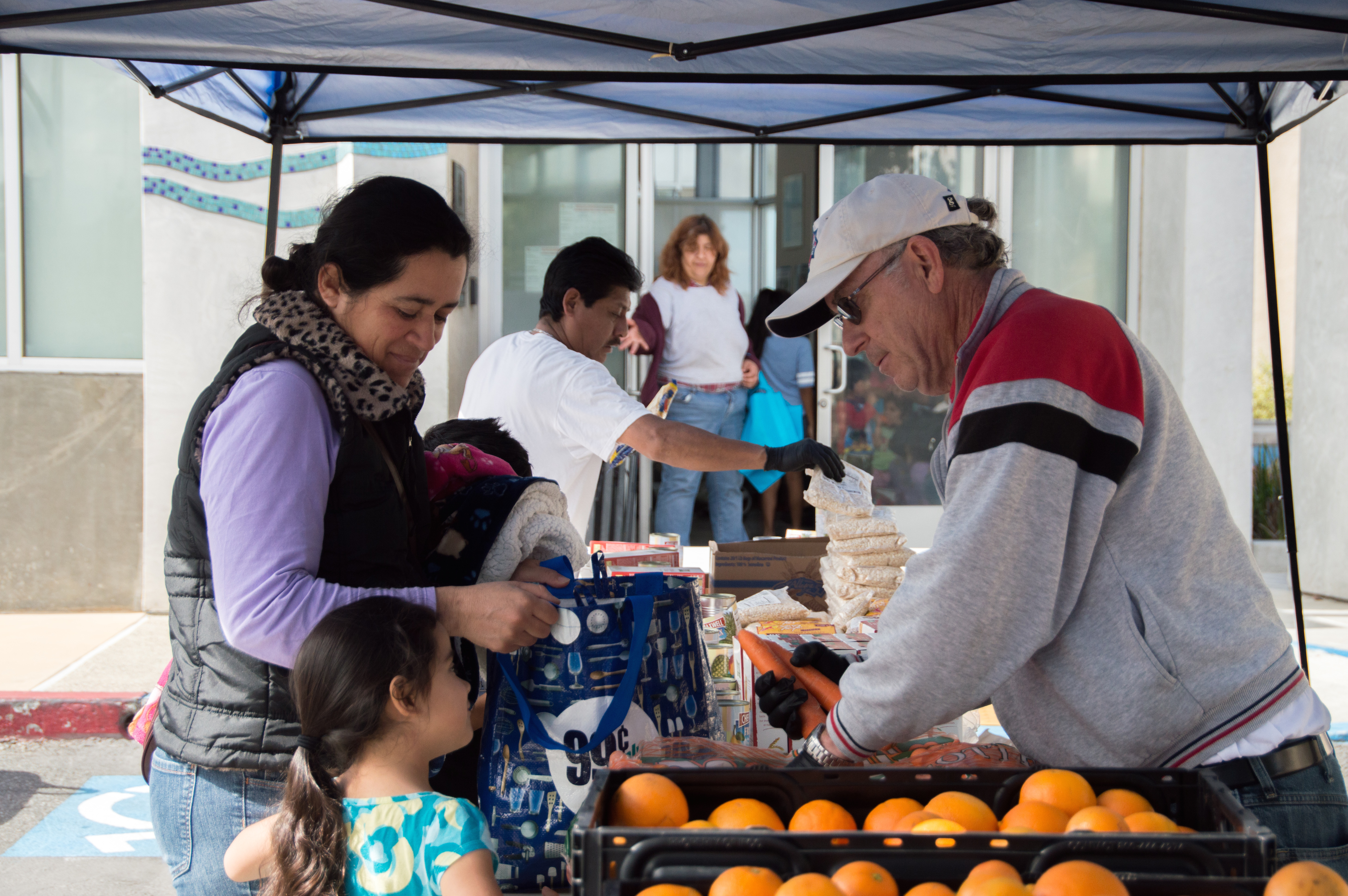 volunteer handing out vegetables at booth
