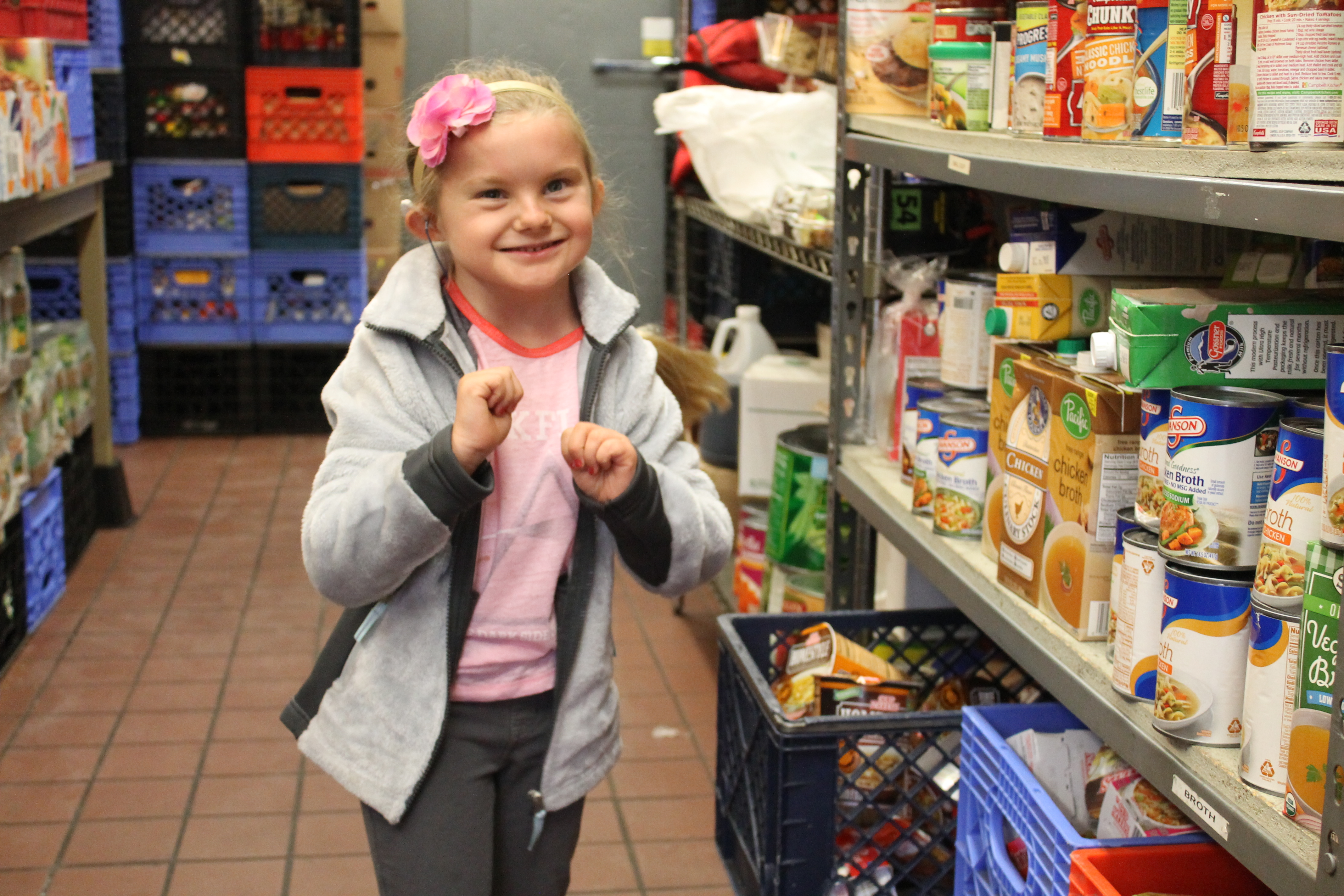 little girl with shelves of food
