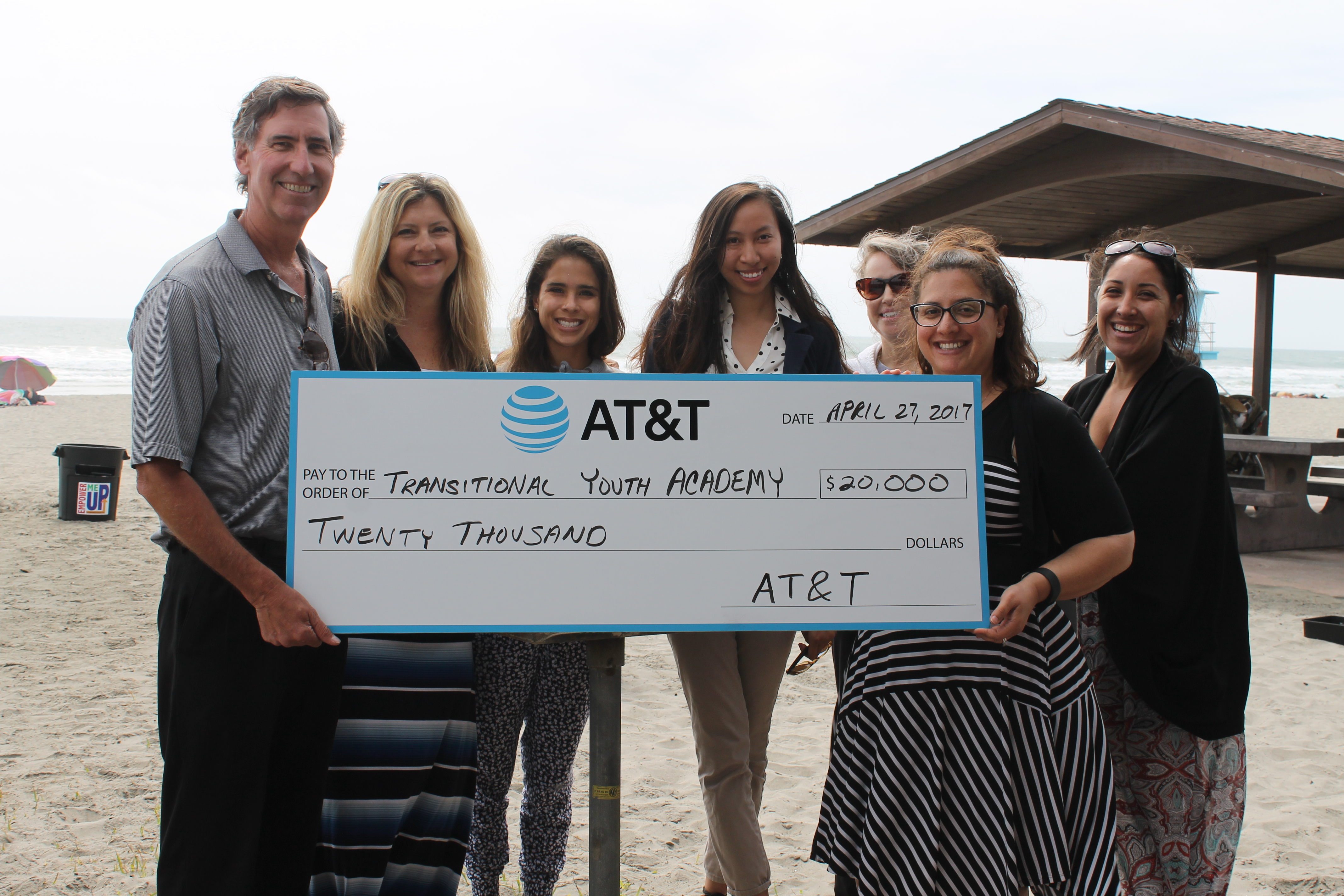 group photo holding large check A T and T giving $20,000 to transitional youth academy