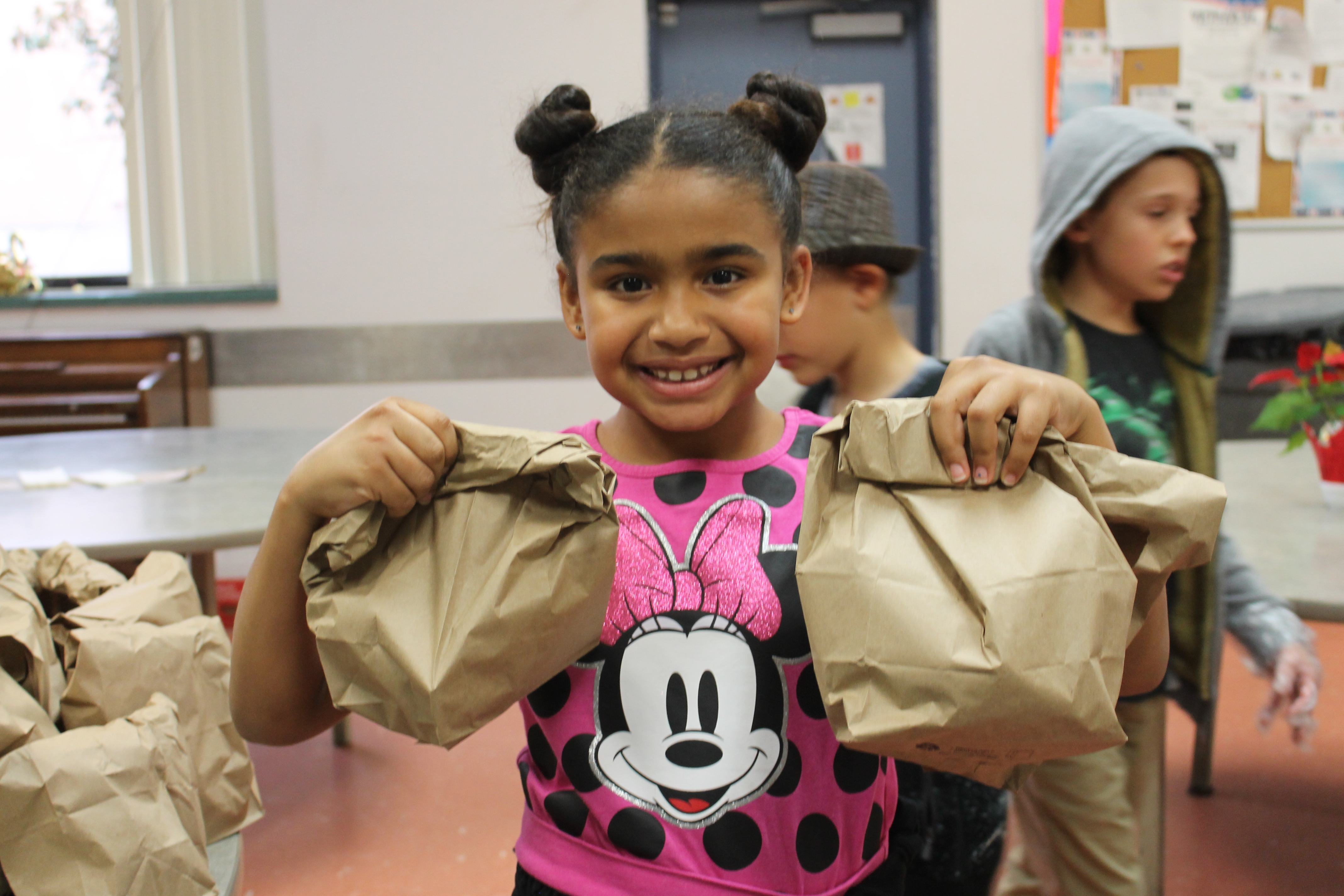 girl child with brown paper bag sack lunches