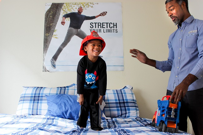 man with son standing on bed
