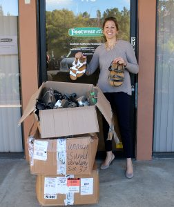 Footwear etc. Director of Marketing, Rebecca Monarch with the over 400 shoes donated to Interfaith!