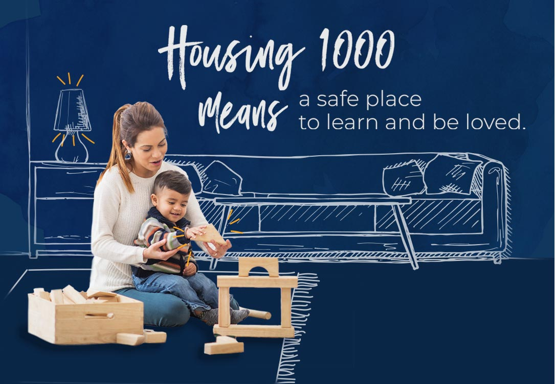 housing 1000 means a safe place to learn and be loved with woman and baby playing with toys