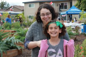 woman and daughter standing by community garden