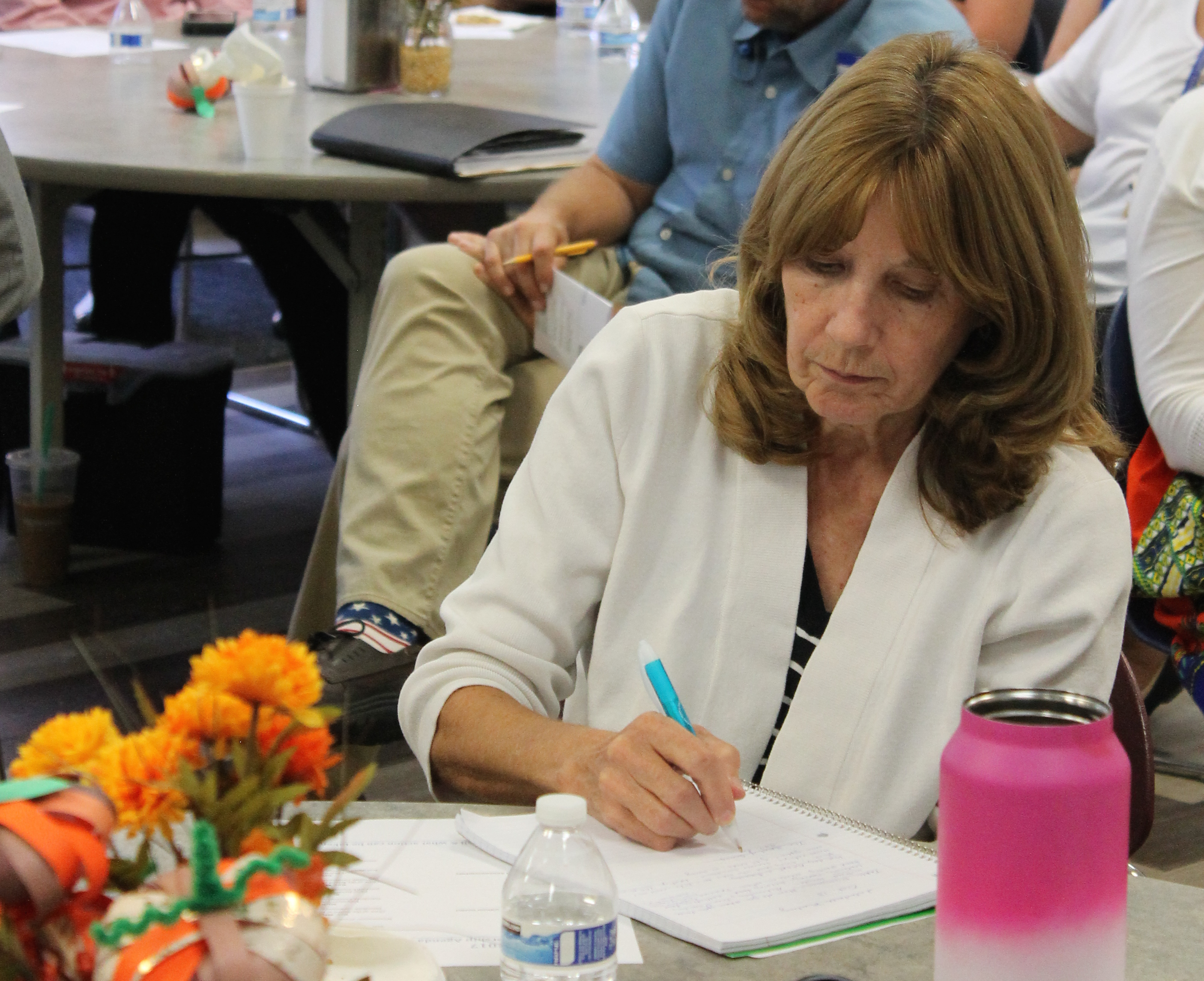 woman writing at general membership meeting