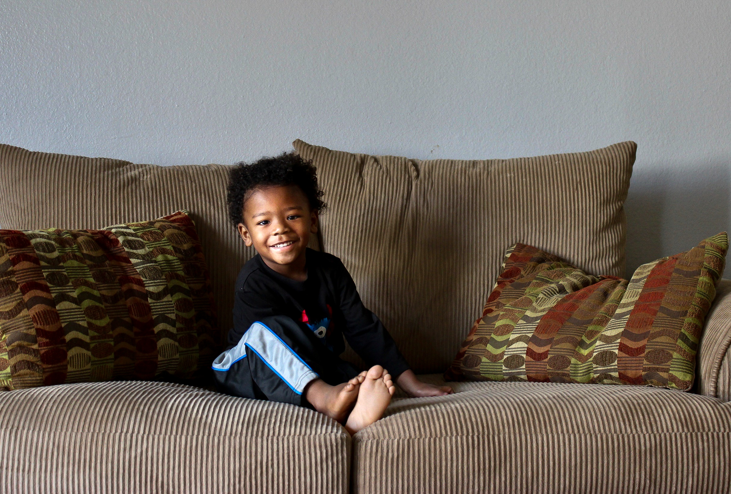 small boy sitting on couch
