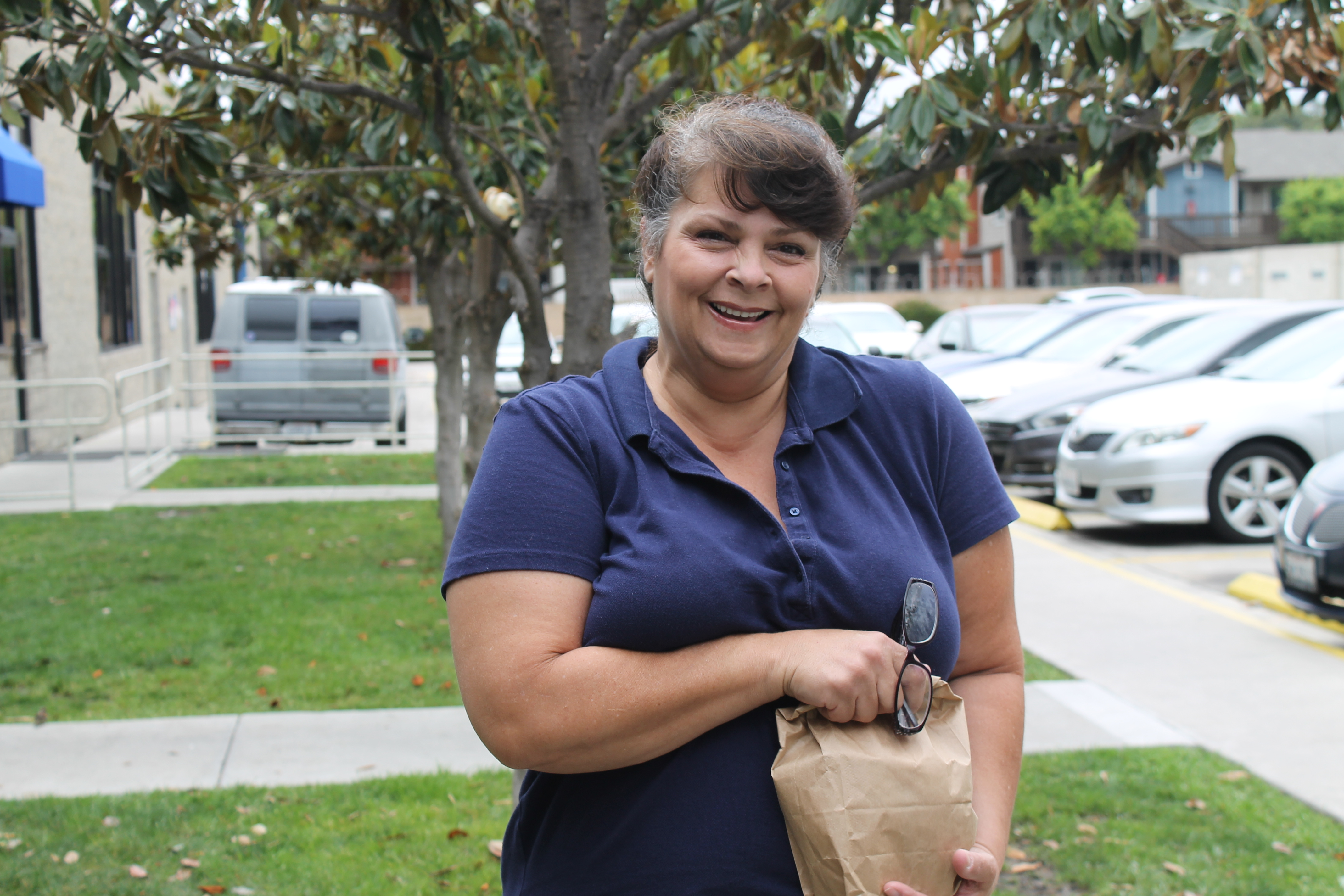 woman with sack lunch smiling