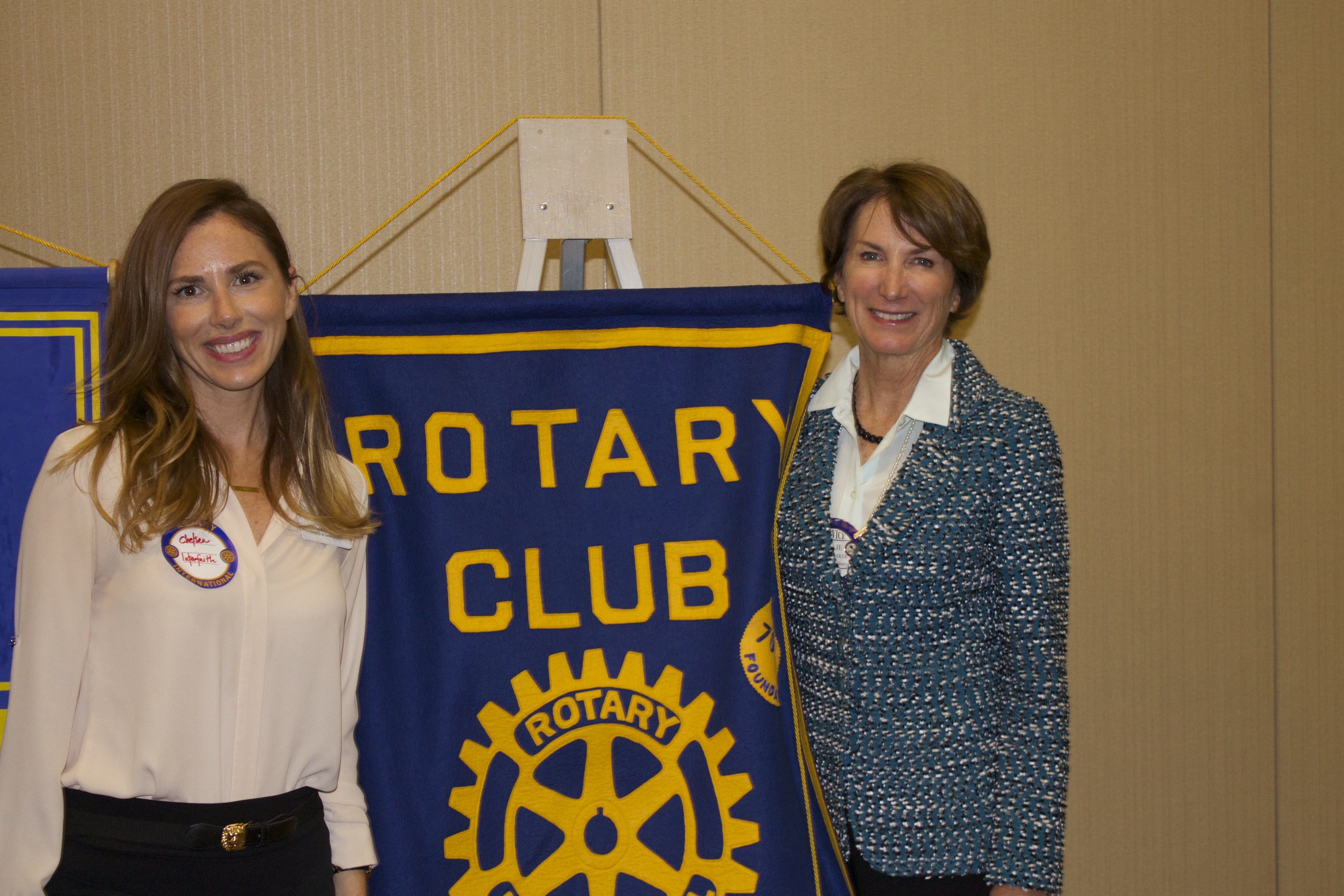 two women standing with rotary club flag